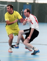 <h5>Attacker and defender tussle in front of the goal</h5>