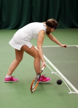 <h5>Tennis player with blindfold bends down to hit low bouncing ball</h5>