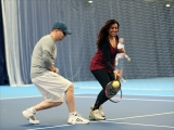 <h5>Tennis try out day, a member hitting the ball and laughing</h5>