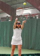 <h5>Tennis player with blindfold  serves the ball high ionto the air</h5>