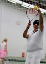 <h5>Tennis player with blindfold holding the ball up to serve</h5>
