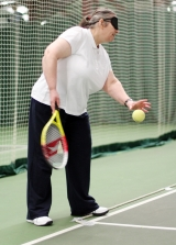 <h5>Tennis player with blindfold bounces the ball </h5>