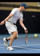 <h5>Tennis player returning a low ball sideways on to the camera</h5>