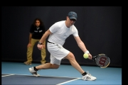 <h5>Tennis player about to return a low ball toward the camera</h5>