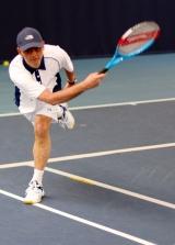 <h5>Tennis player just having returned the ball running toward the camera</h5>