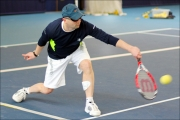 <h5>Tennis player in a baseball hat returns a low bouncing ball</h5>