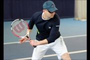 <h5>Close up  of Tennis player in a baseball cap getting ready to return the ball</h5>