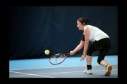<h5>Tennis player bending down to return the ball</h5>