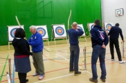 <h5>VI archers lined up and aiming at the targets with their trainers / Helpers </h5>