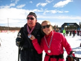<h5>Skier and guide showing off their medals</h5>