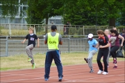 <h5>Runners and Guide Runners in a track event with guide clapping in foreground</h5>