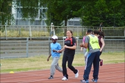 <h5>Runner and guide reach the finish line smiling at a track event  finish line with guide clapping in foreground</h5>
