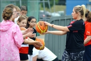 <h5>Volunteer hands out a basket ball to a line of under 18s at the festival</h5>