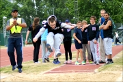 <h5>Under 18 does a Long Jump flying through the air toward the camera , with a group watching from behind at the festival</h5>