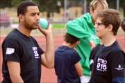 <h5>Athlete with shot put in hand feeliing the weight while talking</h5>