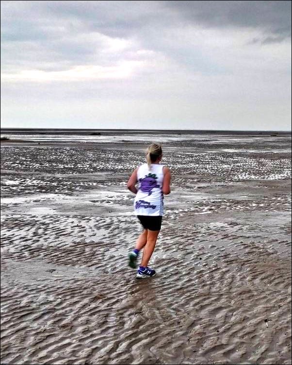 Kelly Barton running on the beach without a guide