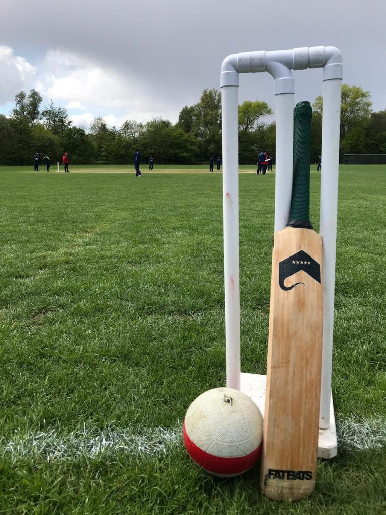 Wicket, bat and ball with the cricket match in the background