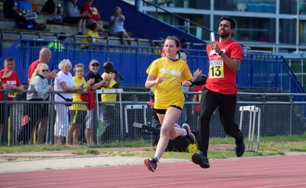 Guide and Naqi Rizvi speeding along track event Metro Blind Sport's 43rd Athletics Open