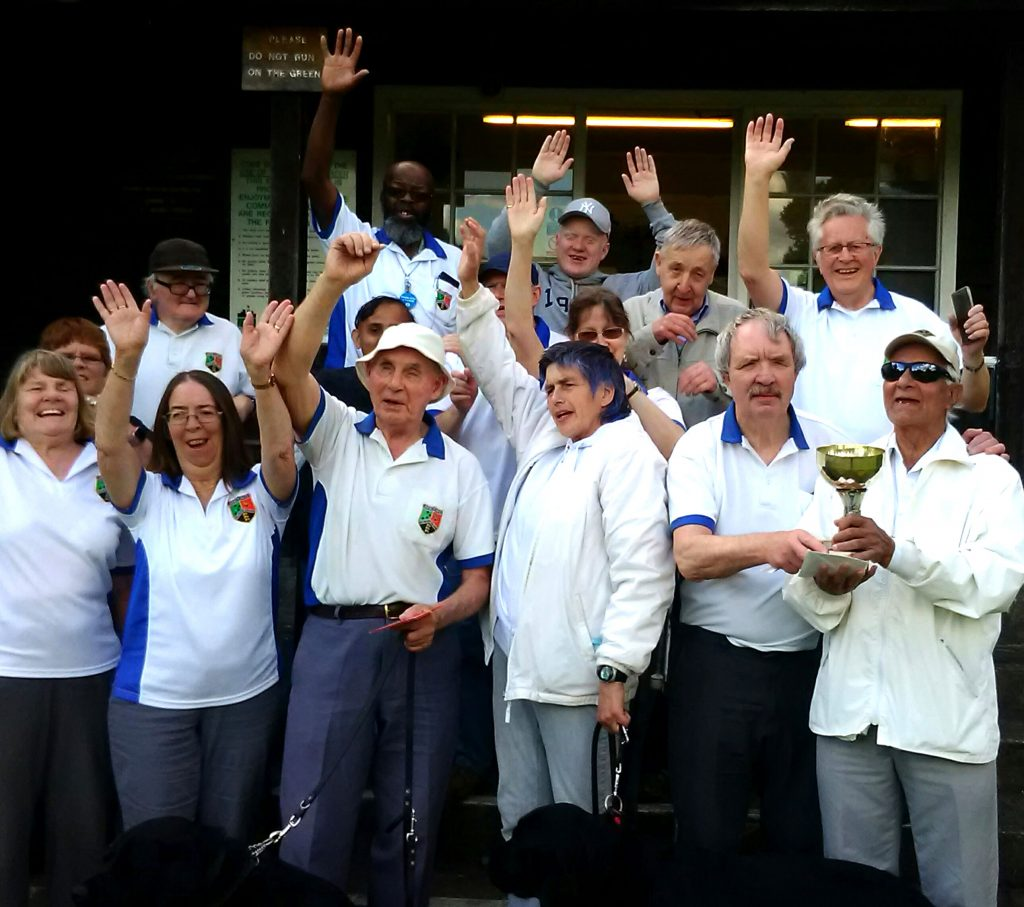 Group photo with smiles hands in the air and a trophy at Ravenscourt Park Bowls Club Metro Pairs Competition 2019