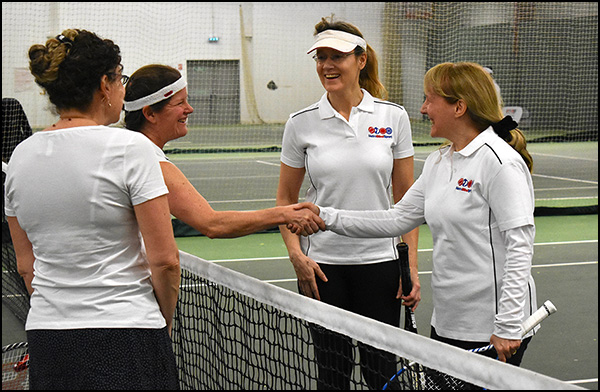 Tennis Doubles Smiling and Shaking hands over the net