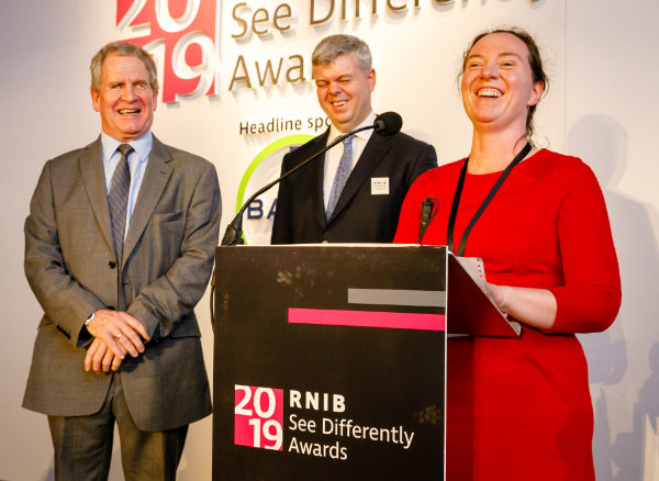 Mike Brace laughing at the podium with the presenters at the RNIB See Differently Awards 2019