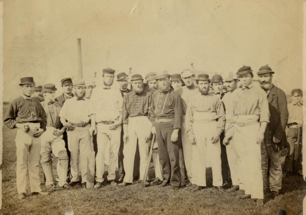 Group photo of cricketers (mostly) in their whites, possibly on Tottenham Marshes c.1865-70