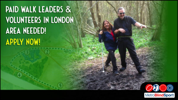 Photo show a walking guide and his walking partner who is holding her white cane, both are laughing out loud as they cross a very muddy area in a wood text says Paid walk leaders & volunteers in London needed! Apply Now!