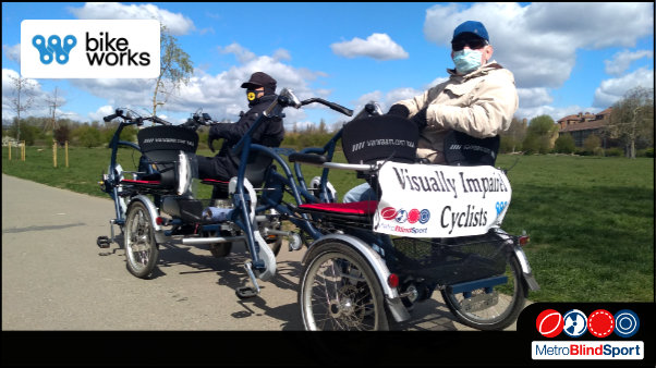 Photo of an Ride side by side ebike with a sighted masked pilot, and passenger with one free seat available, they are in a park with blue sky. At the back of the bike there is a banner with the text saying Visually Impared cyclists - Cycling Ride Side-by-Side with Bikeworks & Metro!