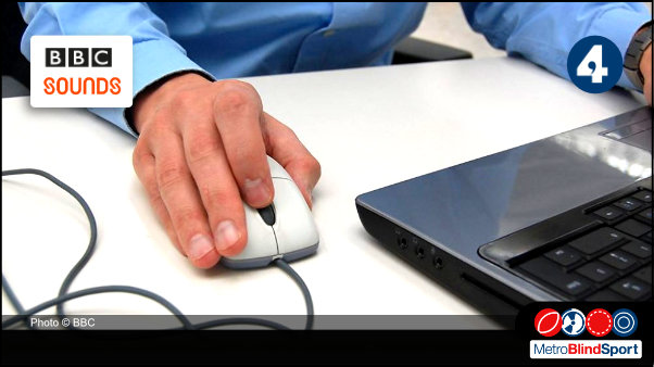 photo of a hand on a mouse next to a laptop -BBC In Touch - Technology Special