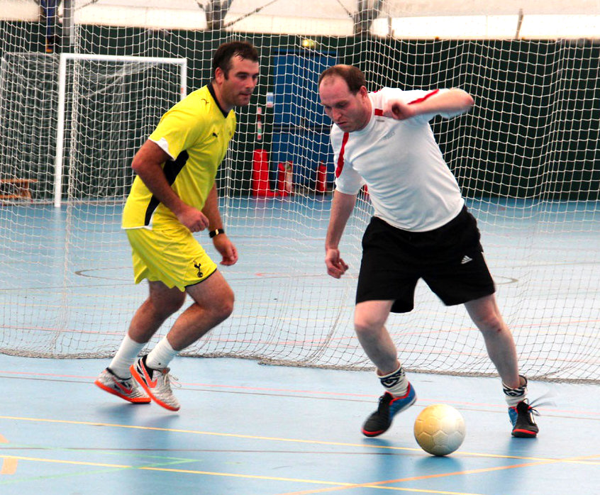 Photo of Gareth Jones and Mark Russell playing Futsal, Mark has the ball and Gareth is coming up behind him.