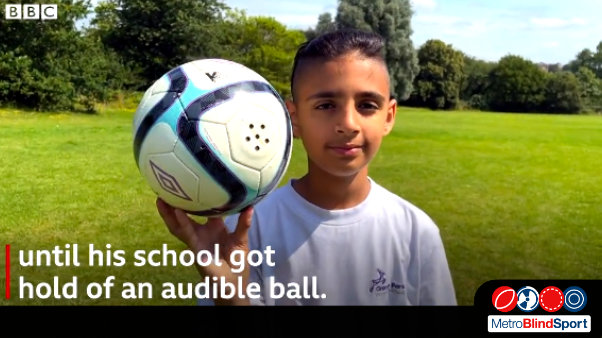 photo of Mikey Poulli holding the aduio football on the football pitch