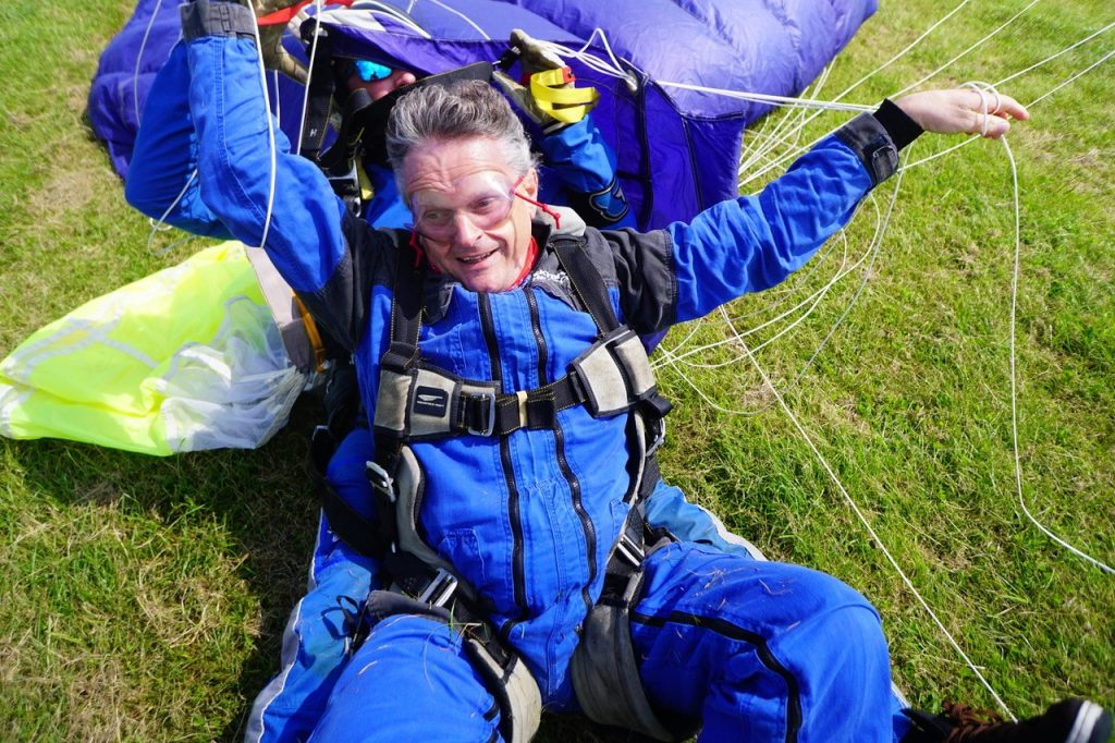 Chris smiling on the ground untangling himself from the lines of the parachute