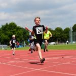 Winner of a under 18 track event getting to the finish line