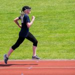 Paticipant getting into her stride in the sunshine in a track event
