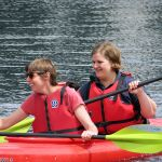 laughing on the water in life jackets while kayaking
