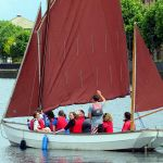 Participants out on the water in a medium sized Sailing Boat