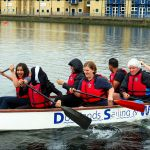 Side on Photo of Participants paddling in a long rowing boat with the front paddles Laughing